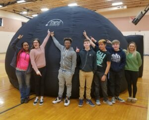 Students stand in front of StarLab inflatable planetarium